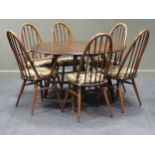 An Ercol Model 377 dark stained beech and elm drop leaf dining table and six (4 + 2) chairs