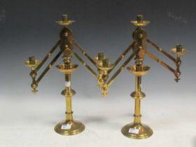 A pair of adjustable three light brass candelabra