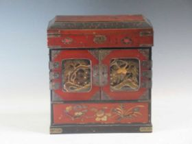 A Japanese meiji period lacquered table cabinet, the two doors enlcosing drawers, with side