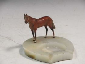 An Asprey Of London 1930's Art Deco style onyx ashtray, mounted with a cold painted figure of a