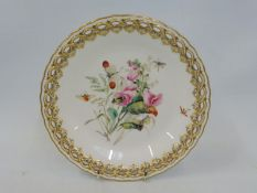 A Royal Worcester cabinet plate with a pierced gilded border and central hand painted floral