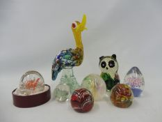 A selection of glass paperweights plus two glass animal ornaments.