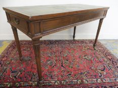 A mahogany rectangular leather topped writing desk with a single drawer to each end, raised upon
