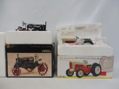 Two boxed tractors, one Ford Golden Jubilee, the other a Farmall.