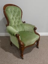 A Victorian walnut gentleman's Armchair, with spoon shaped button back, scrolled arms leading to