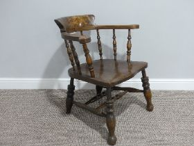 A late 19thC ash and elm smokers bow Armchair, with spindle gallery and sweeping arms, shaped saddle