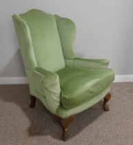 An early 20thC Wing Armchair, in green upholstery, with carved cabriole front supports, 30½in (