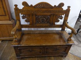 An early 20thC box seat Oak Settle, the two panel front with open scroll arms, foliate carved shaped