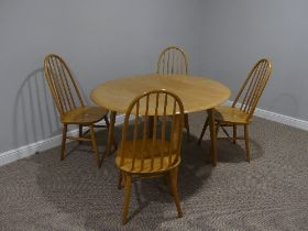 A mid 20thC Ercol style drop leaf oval Dining Table, the top 44in (112cm) x 49in (124.5cm) extended,