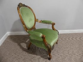 A Victorian walnut showframe open Armchair, with gilt carved decoration, the leaf leaf capped