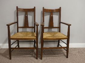A pair of Arts and Crafts oak Carver Chairs, with rush seats, splat back with carved heart motif,