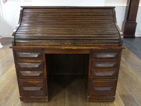 An early 20thC American oak roll top Desk, marked 'Cutler', the serpentine tambour front revealing