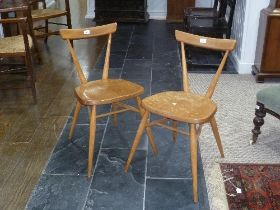 A pair of mid 20thC light elm and beech Ercol Stacking Chairs, both with holographic sticker labels,
