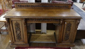 An early 20thC Continental carved oak pedestal Sideboard, with single central drawer, heavily carved