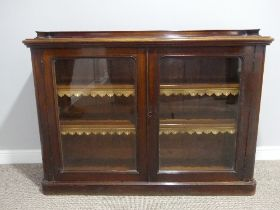 A Victorian mahogany two door glazed Bookcase, the two adjustable shelves with gilt leather