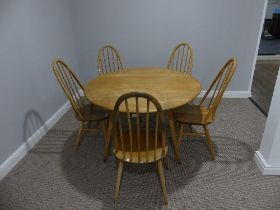 A mid 20thC Ercol elm and beech drop leaf Dining Table, the elm plank top on splayed tapering