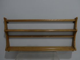 A mid 20thC Ercol two tier wall hanging Plate Rack, with holographic sticker, 38in (97cm) long, 20in
