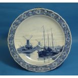A large Dutch Delft Charger, with gadroon shaped edges, hand painted in blue tones with a scene of