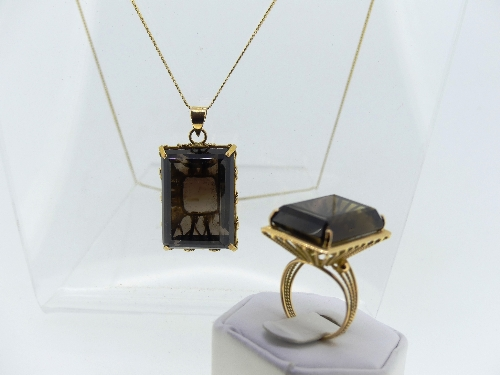 A rectangular smokey quartz Pendant, claw set in a wirework yellow metal mount, all unmarked, the