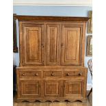A George III oak Housekeepers Cupboard, the two fielded panel doors with mahogany banding opening to