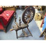 A vintage oak Spinning Wheel, 34in (86.5cm) long, 22in (56cm) wide, 39in (99cm) high.