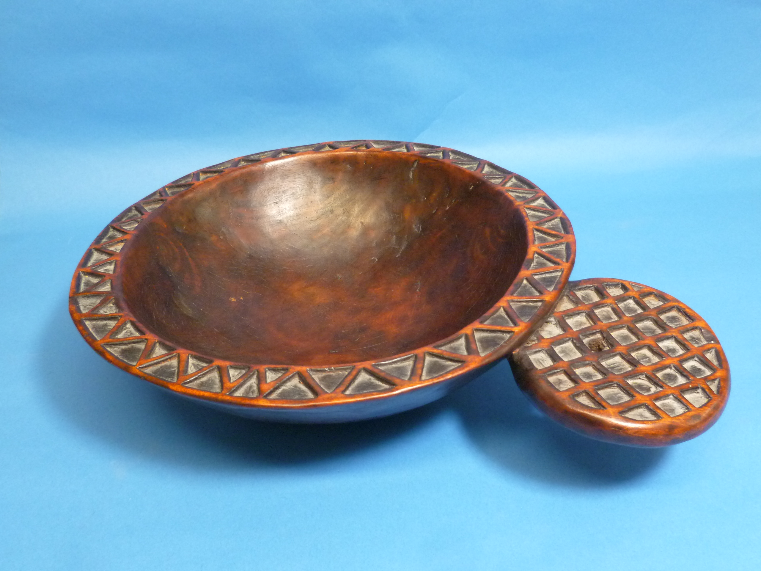 A Tribal geometrically-carved wooden circular Bowl, with protruding circular handle (carved from