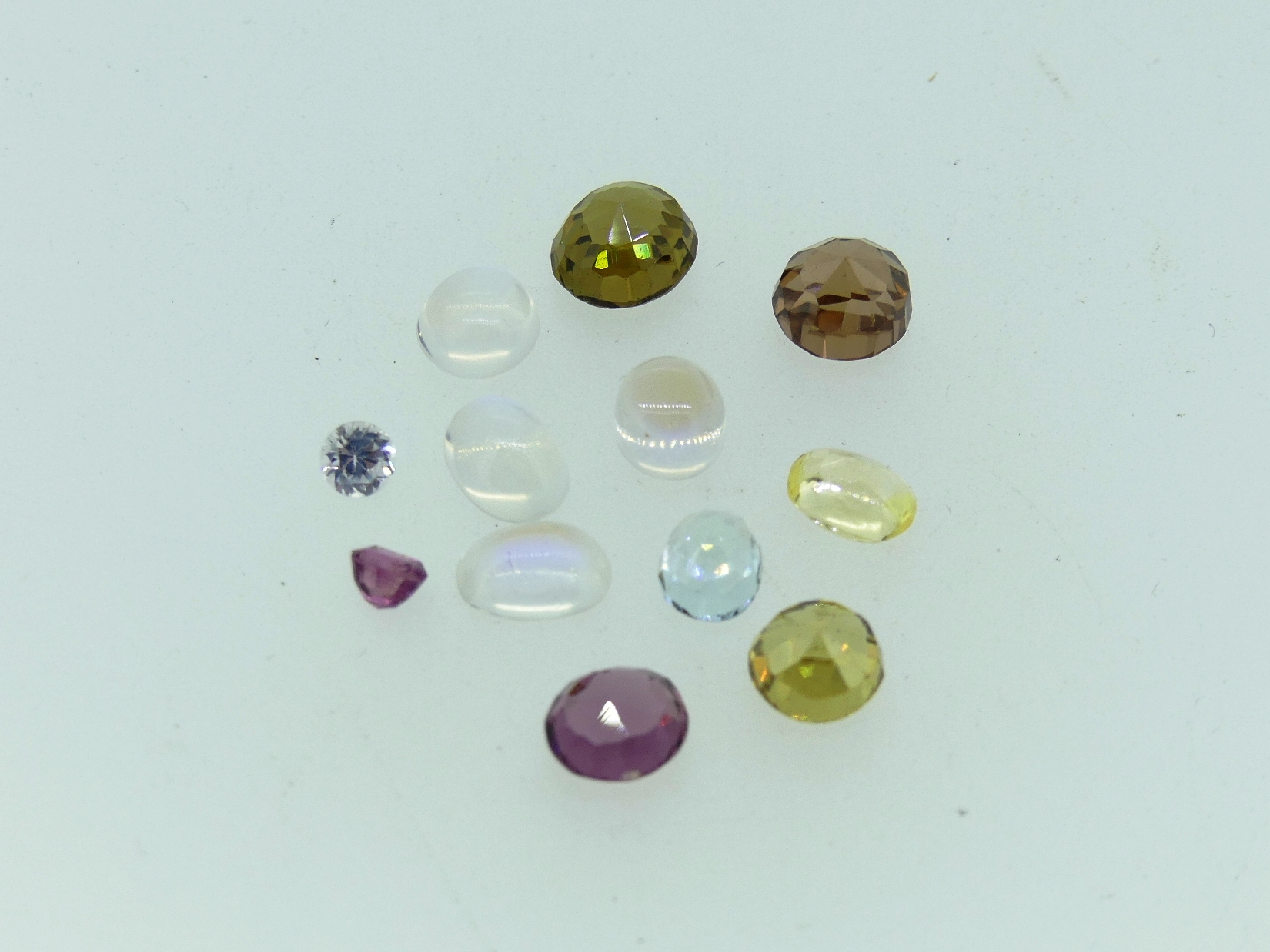 A collection of twelve loose semi-precious stones, including four moonstone, three testing as