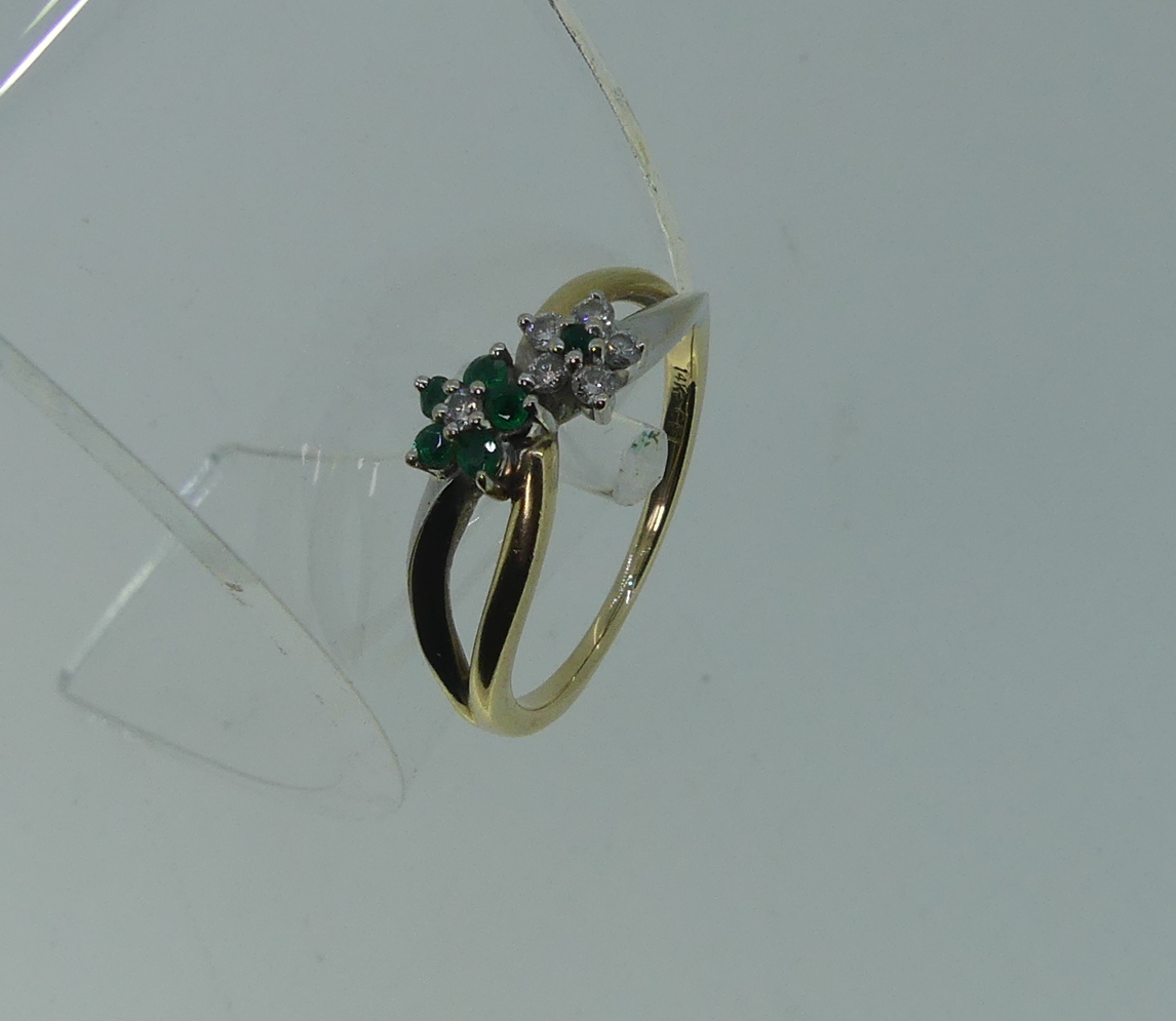 A small 14kt yellow gold Ring, set on the cross with two flowerheads, one of five emeralds with - Image 3 of 3