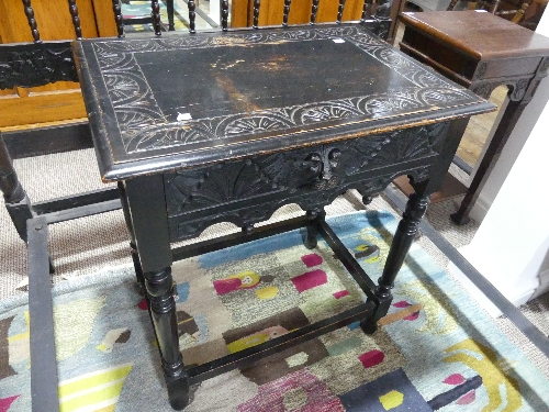 A late 19thC stained oak Side Table, with heavily carved top upon central drawer boasting Green