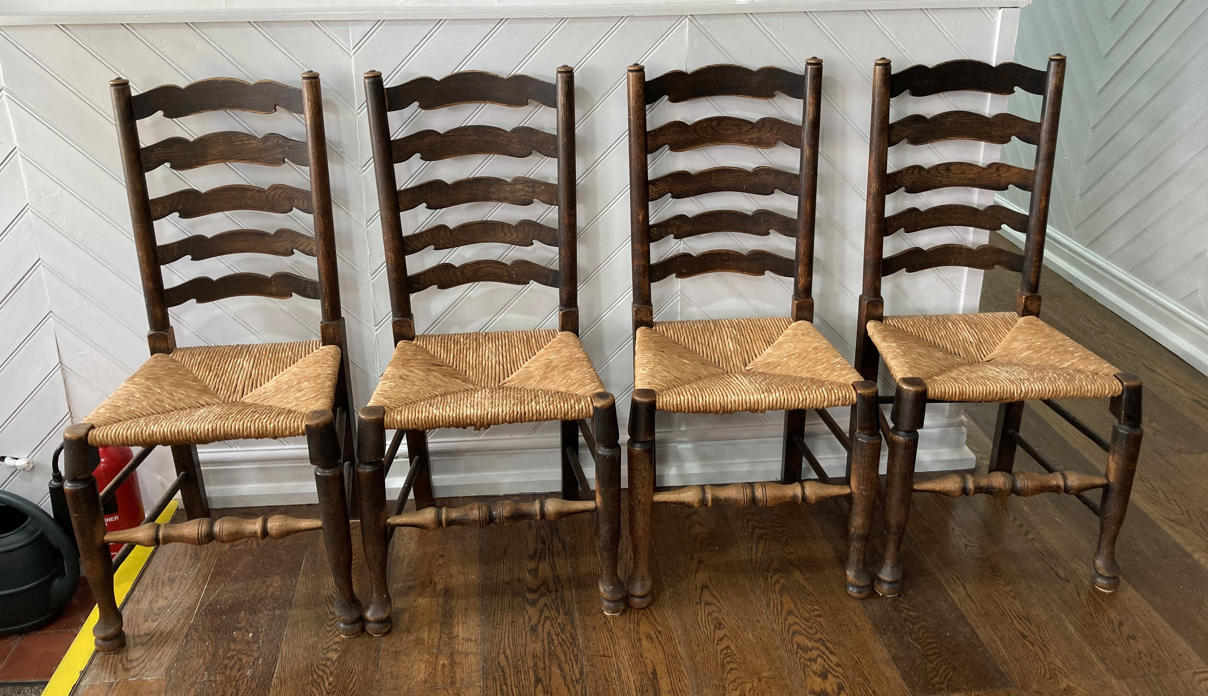 A set of four early 20thC oak Ladder-back Chairs, the laddered back over the envelope rush seats,