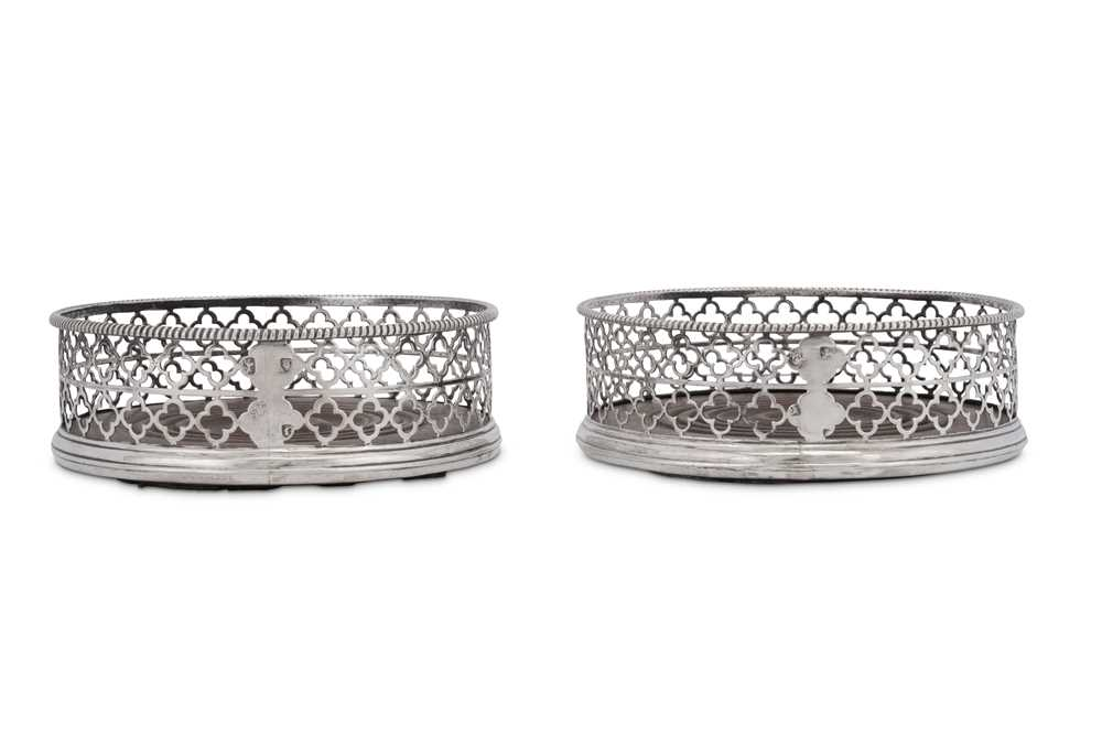 An unusual pair of George III sterling silver wine coasters, London 1768 by Thomas and William Chawn