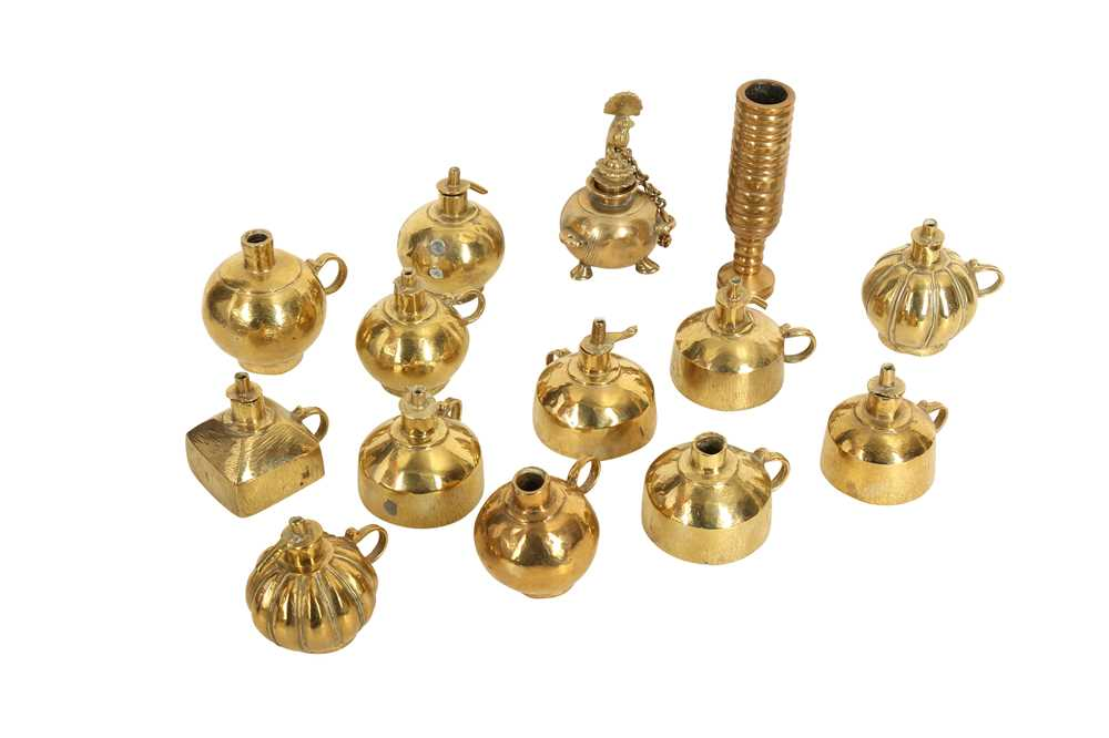THIRTEEN BRASS OIL LAMPS AND A TUBULAR BRASS ELEMENT India, late 19th - 20th century