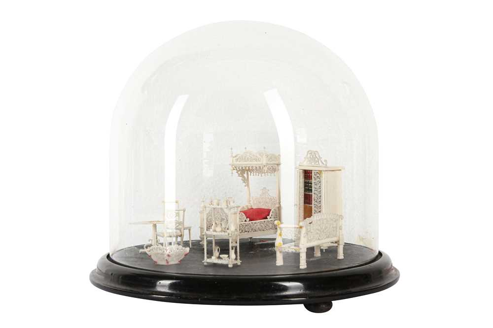 A 19TH CENTURY CARVED BONE SET OF MINIATURE FURNITURE WITHIN A GLASS DOME