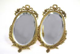 A pair of gilt metal framed oval mirrors, with easel backs,