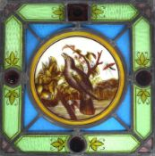 A stained glass panel, circa 1900, depicting a bird in song perched on a branch,