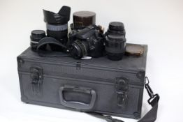 A Nikon D40 camera with accessories in a carry case and two vintage Kodak cameras