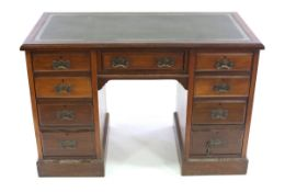 An Edwardian pedestal desk, fitted nine drawers around a kneehole,