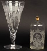 A large glass etched with grapes and vines on an air twist stem,