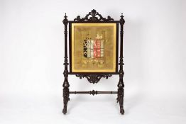 A Victorian armorial fire screen, the needlework panel with the crest of arms of Foljambe,