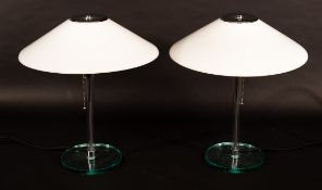 A pair of glass table lights, with opaque glass conical shades and circular bases,