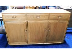 An Ercol elm sideboard with three drawers & cupboa