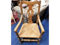 An early 20thC. oak throne style chair with rush s