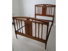 An Edwardian walnut double bed with carved decor