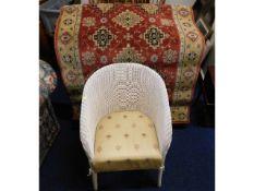 A Lloyd Loom style chair twinned with a wool rug b
