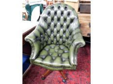 A leather Chesterfield style swivel bucket chair,