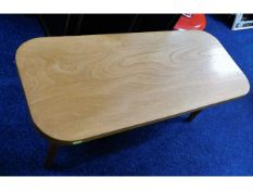 An oak coffee table, fault with one leg 36.25in lo
