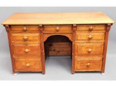 An antique light oak knee hole desk with nine draw