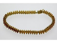 A 9ct gold bracelet set with marquise cut red, yel