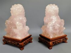 A pair of Tibetan carved pink quartz foo dogs with