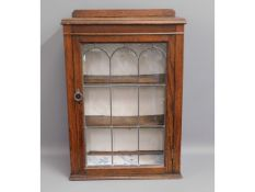 An early 20thC. oak wall cabinet with shelves, 33i